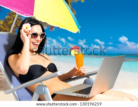 Happy woman on the beach with a laptop computer. Vacation and communication concept. - stock photo