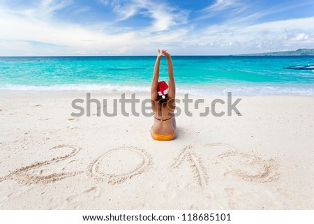 Happy woman on the beach with Santa Claus hat, 2013 - stock photo