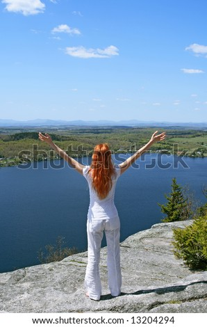 Happy woman on the mountain enjoys beautiful view. - stock photo