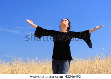 Happy woman on the wheat field. Thanks to heavens/ - stock photo