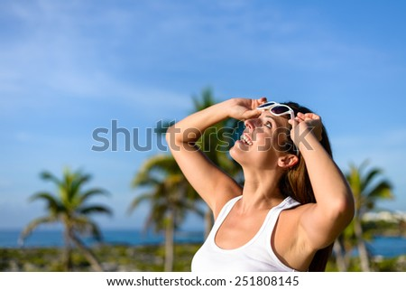 Happy woman on tropical travel having fun and looking up raising sunglasses. Brunette girl on caribbean vacation. Riviera Maya, Mexico. - stock photo