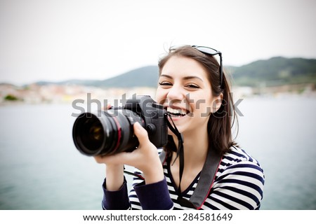 Happy woman on vacation photographing with a dslr camera on the beach and smiling - stock photo