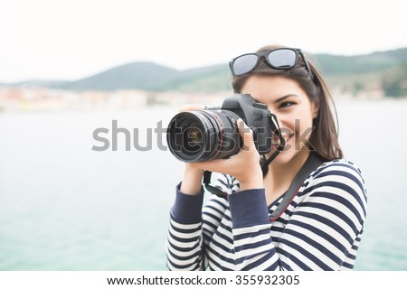 Happy woman on vacation photographing with a dslr camera on the beach and smiling.Vacation photography travel concept - stock photo
