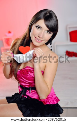 happy woman on Valentine's Day with a white paper a ship with a heart. - stock photo