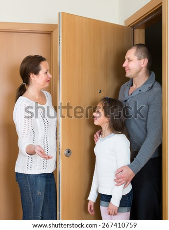 Happy woman opening door for coming husband with daughter - stock photo