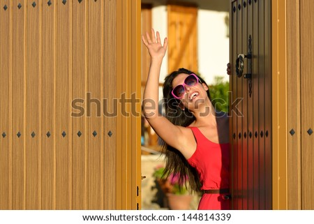 Happy woman opening her country house door to welcome guests visitors. Charming caucasian brunette girl good bye standing in home entrance. - stock photo