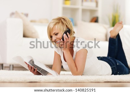 Happy woman ordering something from catalog - stock photo