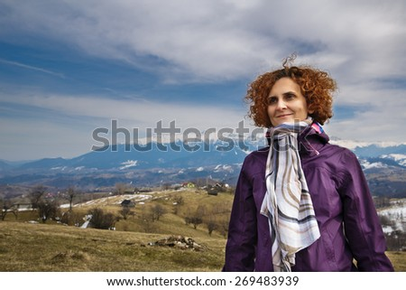 Happy woman outdoor portrait with mountains on background - stock photo