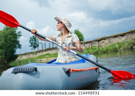 Happy woman paddling a kayak on the river, enjoying a lovely summer day