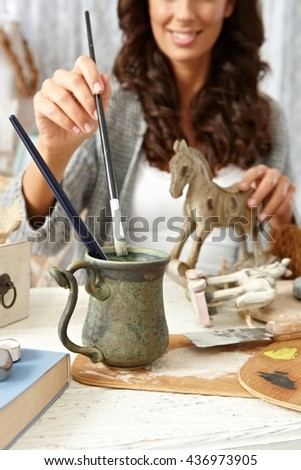 Happy woman painting wooden horse at home in vintage style. - stock photo