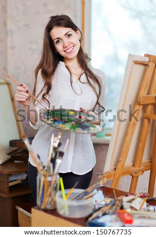 Happy  woman paints on canvas with oil paints in workshop - stock photo