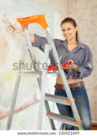 Happy woman paints wall with brush