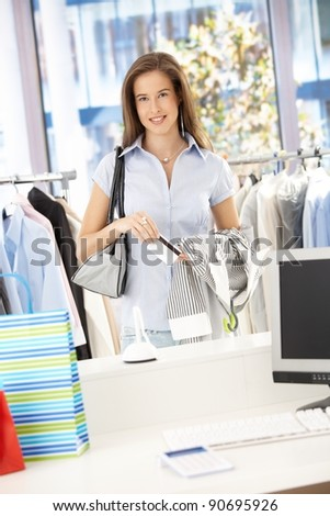 Happy woman paying her shopping with credit card in clothes store, looking at camera, smiling.?