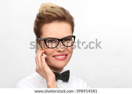 Happy woman phone talking. Portrait of a smiling lady in bow tie & glasses using mobile phone - stock photo