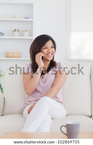 Happy woman phoning while sitting on a couch in a living room - stock photo