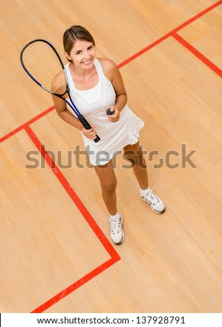 Happy woman playing squash at the court - stock photo