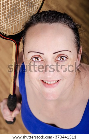 Happy woman playing squash in a gym, holding racket and smiling. - stock photo