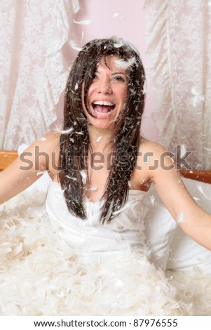 Happy woman playing with feather and down stuffing and laughing. - stock photo