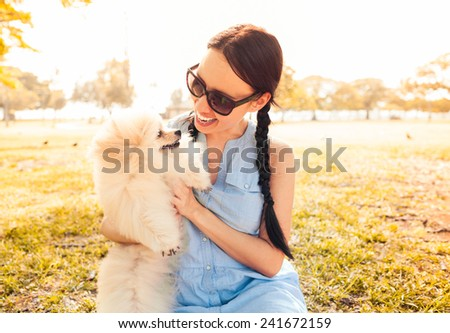 Happy woman playing with her pet dog - stock photo