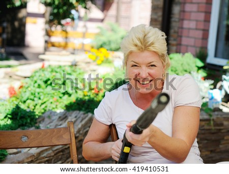 Happy woman playing with kids and watering in domestic garden at summer day - stock photo