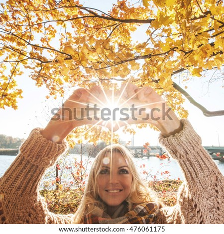 Happy woman playing with sun in autumn park