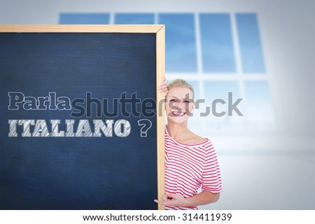 Happy woman pointing to card against bright white room with windows - stock photo