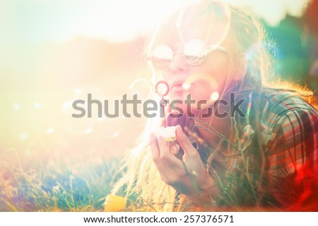 Happy Woman Portrait blowing Soap Bubbles. Vintage retro photo at Summer time - stock photo