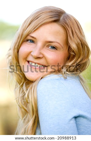 happy woman portrait smiling outdoors in a park - stock photo