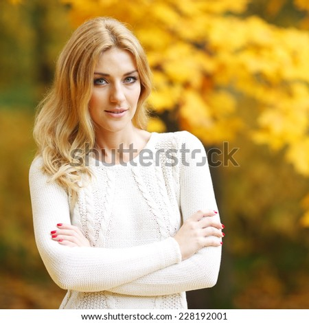 Happy woman posing in autumn park on yellow trees background - stock photo