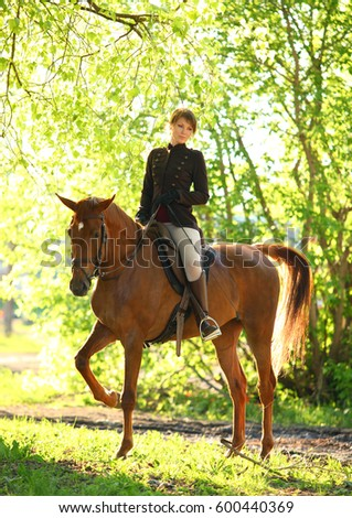 Happy woman posing on top horse in forest at sunset back light