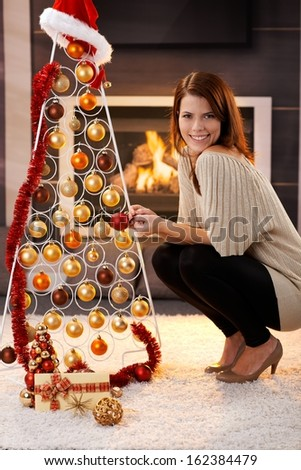 Happy woman posing with design christmas tree with tinsel and bulb and Santa hat and gift, in cosy living room with fireplace. - stock photo