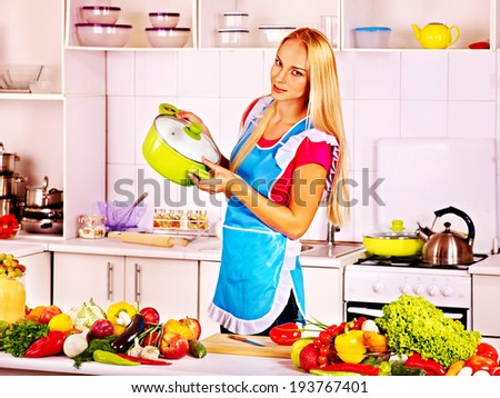 Happy woman preparing food at kitchen. - stock photo