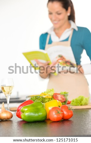 Happy woman preparing recipe vegetables wine kitchen cooking book - stock photo