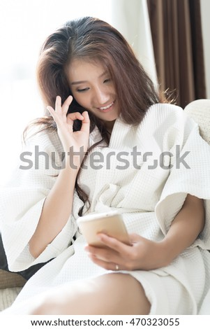 Happy woman presenting OK sign while video call with her smartphone.