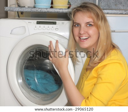 happy woman puts linen in a washing machine
