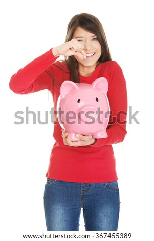 Happy woman putting a coin to piggybank. - stock photo