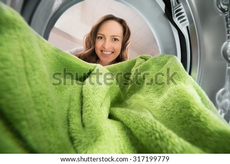 Happy Woman Putting Green Towel View From Inside The Washing Machine Appliance - stock photo