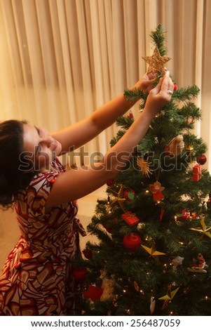 Happy woman putting star on the family Christmas tree. - stock photo