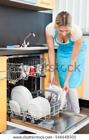 Happy Woman Putting Utensils In Dishwasher For Cleaning
