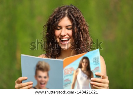 Happy woman reading a magazine in a park with a green background              - stock photo