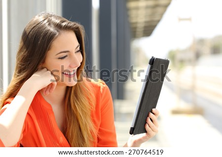Happy woman reading a Tablet or ebook in a train station while is waiting for public transport - stock photo