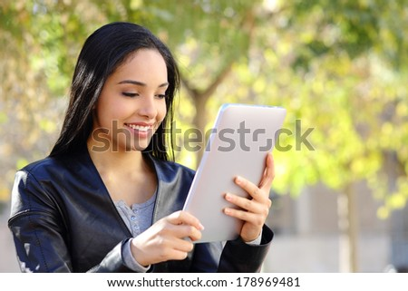 Happy woman reading a tablet reader in a park with a green background         - stock photo