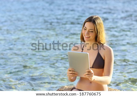 Happy woman reading a tablet reader on the beach seaside with water in the background    - stock photo