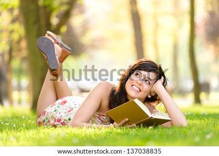 Happy woman reading and holding  story book in fresh green park on spring or summer. Caucasian brunette beautiful girl smiling and day dreaming lying down outdoors. - stock photo
