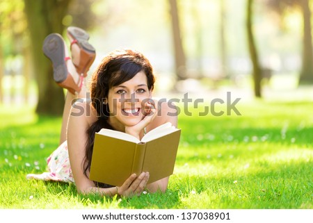 Happy woman reading and holding  story book in fresh green park on spring or summer. Caucasian brunette beautiful girl smiling and day dreaming lying down on grass outdoors. - stock photo