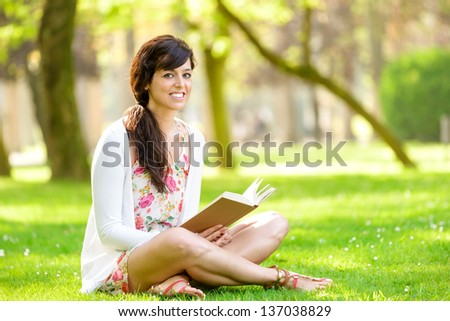 Happy woman reading and holding  story book in fresh green park on spring or summer day. Caucasian brunette girl smiling and enjoying sitting on grass outdoors. - stock photo