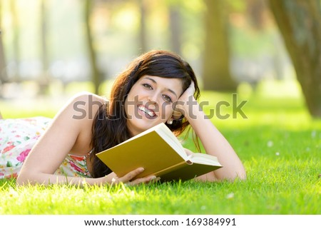 Happy woman reading book lying down on grass in park. Brunette beautiful girl relaxing and enjoying leisure on spring or summer outside. - stock photo