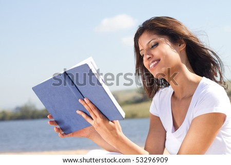 happy woman reading book outdoors - stock photo
