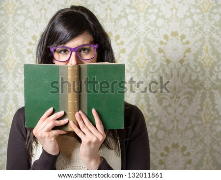 Happy woman reading.  Girl looking over old book on retro background. Student smiling behind old book wearing glasses. - stock photo
