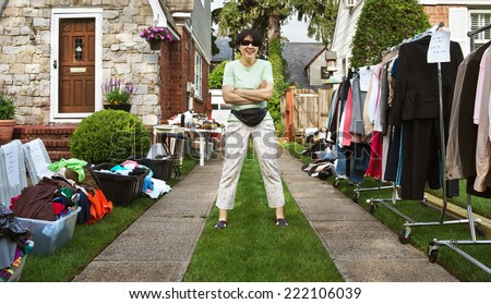 happy woman ready to sell items at yard sale. - stock photo